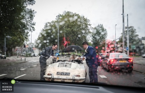 Rotterdam groom and best man making sure the bride doesn't get wet from the rain - putting the top up on the convertible