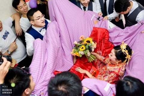 Shaanxi bride being carried in a blanket by the groomsmen