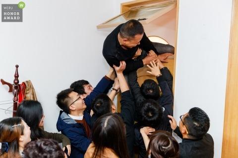 Shaanxi wedding gatecrashers send the groom through an open window above the door