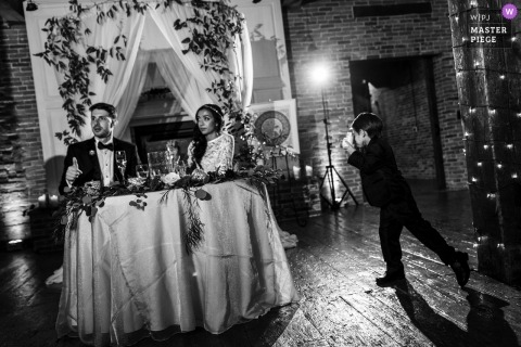 Black and white photo of a small boy with the camera creating an image of the bride and groom at their head table during the reception