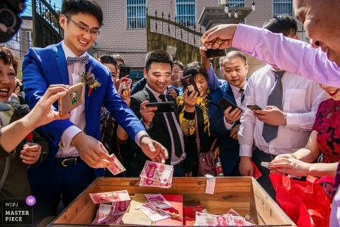 Photograph of wedding guests and family in the China throwing money into a wooden box