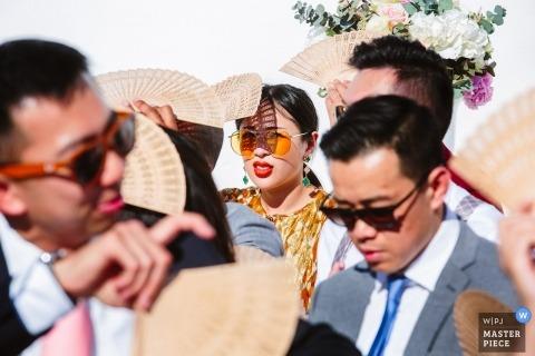 Gasten gebruiken fans om hun gezichten te beschermen tegen de zon op deze buiten Santorini - Griekenland huwelijksceremonie