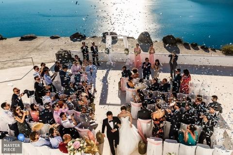 Het einde van deze genade huwelijksceremonie met uitzicht op de zee - het paar loopt uit naar ontploffing van confetti