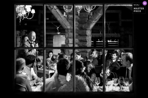 French wedding photo at the reception speeches shot through a glass window in Chamonix, France Alps