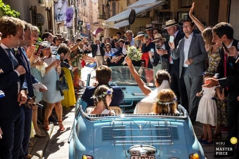 casal de casamento corse dirigindo longe da cerimônia no carro conversível