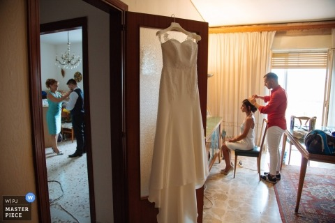 Siracusa bride has her hair fixed as her dress hangs from a door