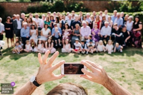 London England Group wedding portrait - piggyback View from behind another photographer