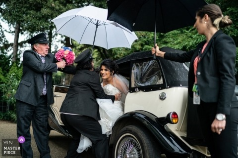Kew Gardens wedding taxi chauffeurs help the bride out of the car while holding umbrellas for her in the rain