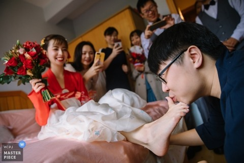 China groom kisses the toe of his soon-to-be bride