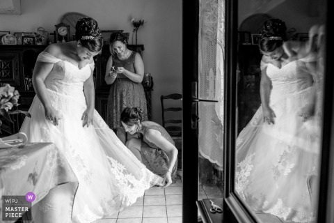 Argentat (France) bride getting help with her dress train - photographer used a mirror reflection