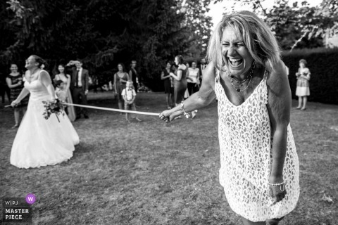 France Noailles outdoor wedding reception party with a bride and guests laughing during games