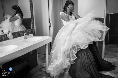 France Hauterive bride getting help under her dress from bridesmaids in a public restroom