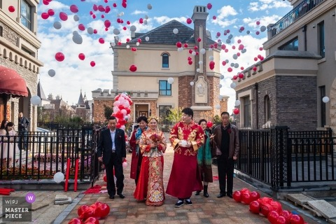 Liaoning China bride walking in the streets as red balloons are left off