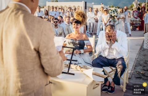 Italian beach wedding ceremony in the hot sun - Photo of the groom with his face in his hands