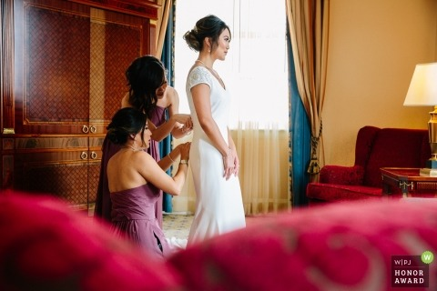 Los Angeles wedding photograph override receiving help closing up the back of her wedding gown