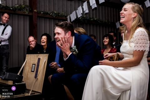 Groningen couple laughing during their wedding reception at the slideshow with photos of the grooms past