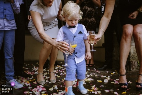 Documentary wedding photograph at Aachen wedding reception with guests clanking glasses with a young boy