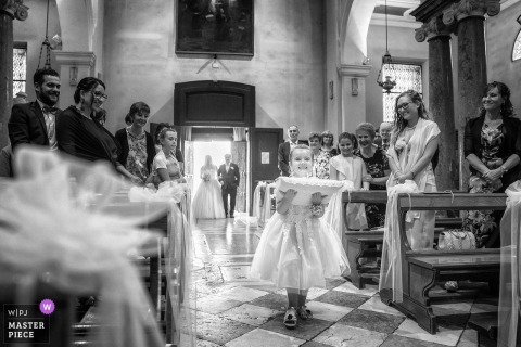 Venice documentary wedding photo of a girl carrying a pillow with a rings into the Church wedding ceremony