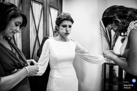 Aurora Lechuga Wedding picture of a bride breathing heavy as she gets help with her dress sleeves