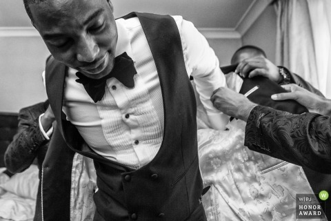 Nigerian wedding in London  - Documentary wedding photograph of grown getting help putting his jacket in London