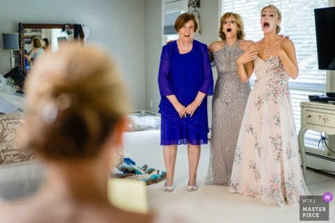 Boston wedding photo of the mothers and maid of honor witnessing the bride's dress for the first time In Massachusetts