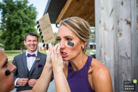 Minneapolis wedding photograph of Bridesmaid getting football stickers put on