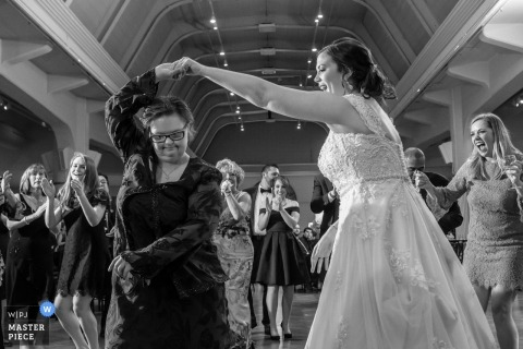 The Henry Ford Museum, Detroit, MI wedding photograph of the bride dancing with the girls at the reception.