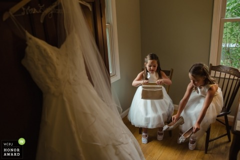 Documentary wedding photograph of two young bridesmaids preparing their shoes and purses at Annapolis