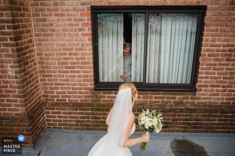 Annapolis documentary wedding photo of the bride passing a window with a woman in it