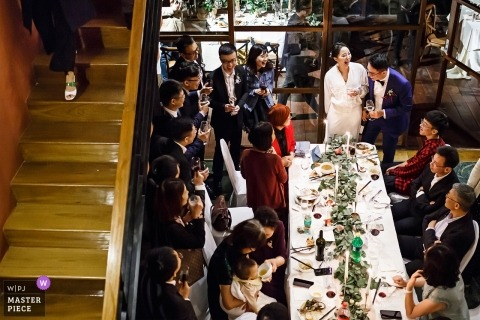 Wedding shoot with Shandong couple surrounded by Friends, family, and the bridal party at one of the reception tables