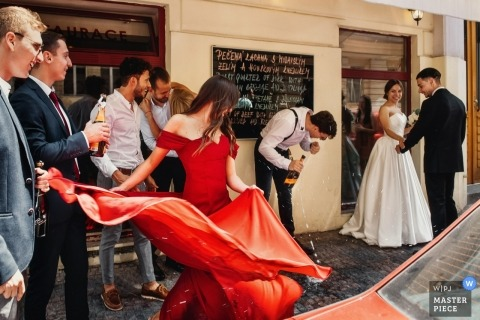 Prague wedding shoot with a couple walking away from drinking guests in the Czech Republic