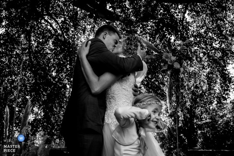 Picture of a couple kissing outdoors with the small girl making a face, by a top Rhederoord wedding photographer