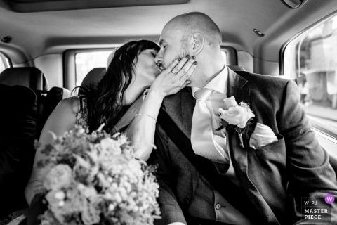 Séance de mariage à Kingston upon Thames avec un couple s'embrassant dans le taxi de mariage