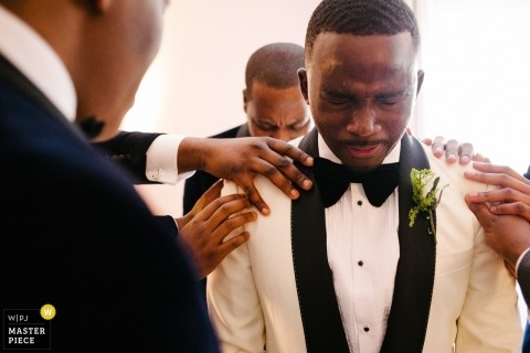 Photo of the groom getting prayed over by groomsmen at the Marriott Hotel Maida Vale, London, UK
