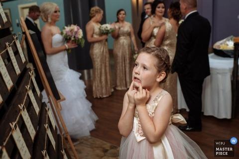 Imagen de periodismo de bodas en Alberta de una niña de las flores mirando por encima de la tabla de asientos en la recepción