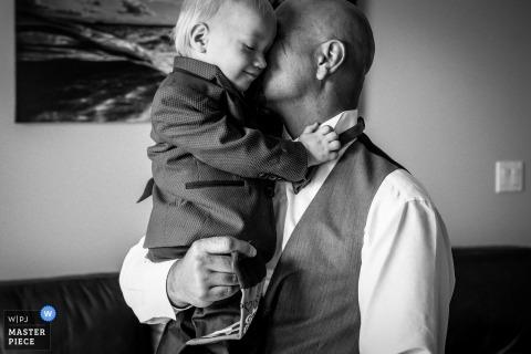 Fotografía documental de bodas en Alberta - Hombre sosteniendo y abrazando a un pequeño portador de un traje.