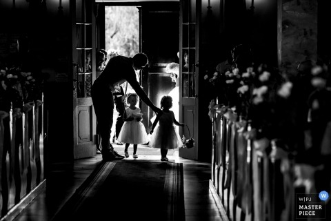 Hungary documentary wedding photo of two flower girls making their way down the aisle in the church