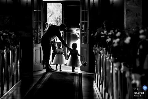 De documentairehuwelijksfoto van Hongarije van twee bloemmeisjes die hun manier onderaan de doorgang in de kerk maken