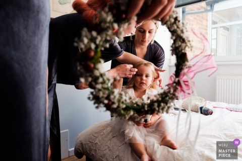 Wedding photo of London flower girl about to receive a crown of flowers