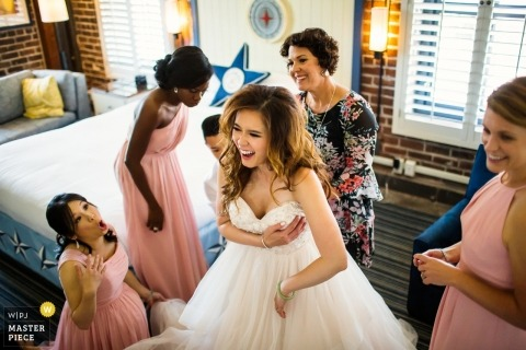 Photo of the bride getting into her dress at the Argonaut Hotel, San Francisco
