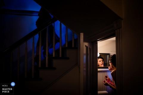 Lenox, MA trouwfoto van de bruid voorbereiding make-up in een badkamer met een kleine spiegel