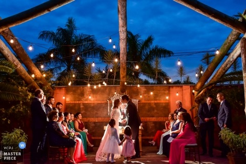 São Paulo wedding photojournalism image of a couple kissing during their outdoor dusk ceremony