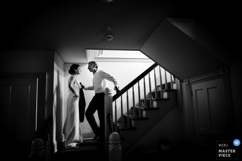 Documentary wedding photograph of a bride waiting at the bottom of the stairs in Lenox, MA
