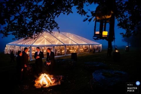 Warren, VT wedding photo of a clear panel tented reception | wedding photograph of an open pit fire at dusk