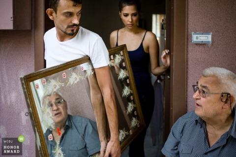 Istanbul-Hochzeitsfoto des Bräutigams, der ein Haus herausstellt, das einen Spiegel für die Braut sich interessiert
