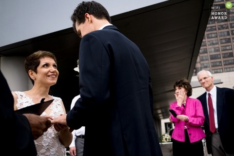 Seattle wedding photojournalism image of a couple during their ceremony exchanging rings