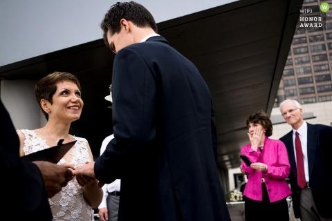 Immagine di fotogiornalismo di nozze di Seattle di una coppia durante la loro cerimonia che scambia gli anelli