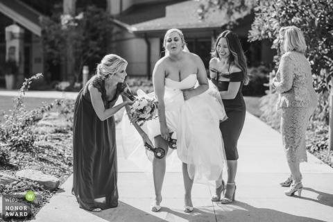 Het huwelijksfoto van Cleveland van een bruid die een ventilator op een zeer hete dag met behulp van