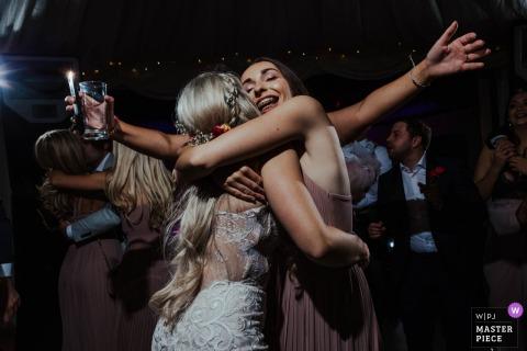 Marleybrook House, Kent wedding photograph of bride hugging bridesmaids on the dance floor.