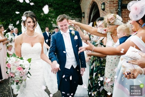 London couple receive handfuls of flower petals thrown at them after their wedding